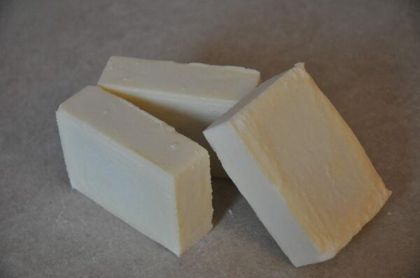 Photos de trois savons Castille de couleur beige clair sur fond pierre