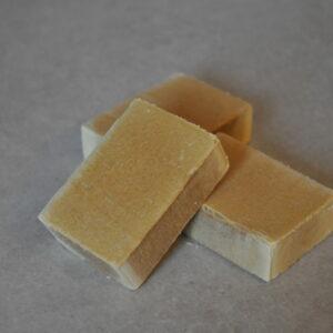 Photos de trois savons Honey de couleur miel sur fond pierre
